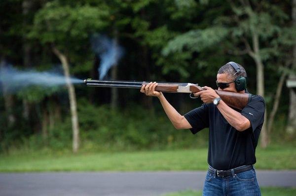 Обама стреляет из оружия.